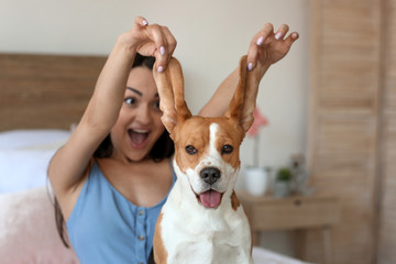 Young woman with cute dog at home