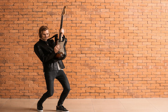 Handsome young man playing guitar against brick wall
