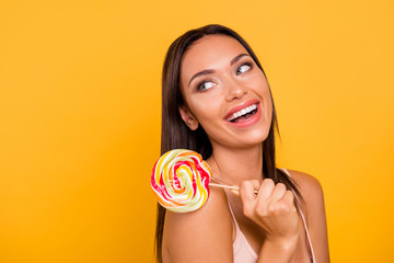 Close up side profile photo beautiful amazing she her lady look side empty space addicted sweets person laugh laughter big lolly pop stick wear casual pastel tank-top isolated yellow bright background Wall mural