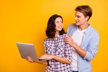 Close up photo of pair in love he him his she her lady boy with computer in hands best intentions looking for web network wearing casual plaid shirts outfit isolated on yellow background