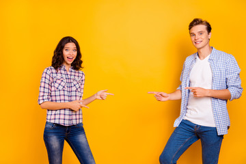 Close up photo of pair stand opposite he him his she her lady boy hands show to empty space on new prizes in store mall shop wear casual denim jeans plaid shirts outfit isolated on yellow background
