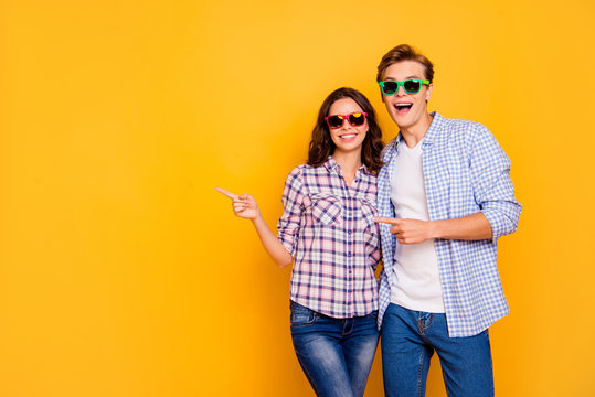 Close up photo of pair in summer specs he him his she her lady boy hands show to empty space on news wearing casual denim jeans plaid shirts outfit isolated on yellow background
