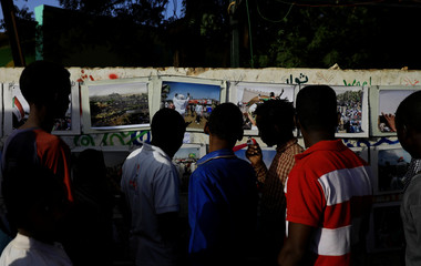 Sudanese examine pictures attached to a wall in front of the defence ministry compound in Khartoum