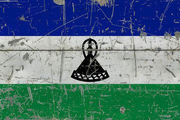 Grunge Lesotho flag on old scratched wooden surface. National vintage background.