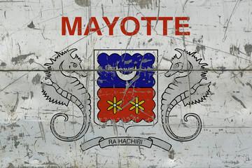 Grunge Mayotte flag on old scratched wooden surface. National vintage background.