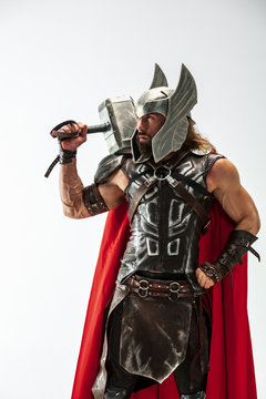 Long hair and muscular male model in leather viking's costume with the big hammer cosplaying Thor isolated on white studio background. Half-lenght portrait. Fantasy warrior, antique battle concept.