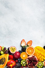 Wall Mural - Healthy raw rainbow fruits background, mango papaya strawberries oranges passion fruits berries on oval serving plate on light kitchen top, top view, copy space, selective focus