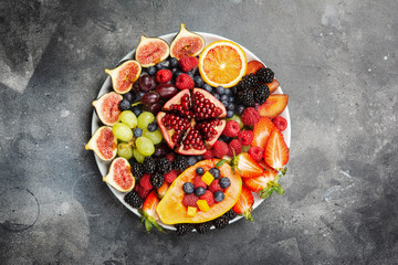 Wall Mural - Delicious fruit platter mango papaya oranges passion fruits berries on round serving plate on dark concrete background, overhead view, selective focus, copy space