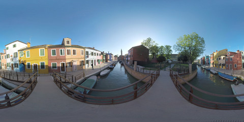 360 photo - Scenic townscape of Burano island in Italy. Rows of painted homes along the canal with boats. View with Campanile of San Martino church. Shot with bell ring