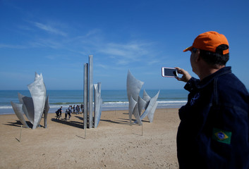 """A tourist takes a picture of a memorial sculpture """"The Braves"""" by artist Anilore Banon at Omaha Beach, in Colleville-sur-Mer"""