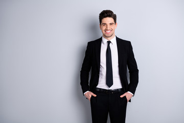 Portrait of independent feel glad successful ceo representative feel glad content place hands fingers palms in pockets modern black trousers fashionable outfit isolated over he his background