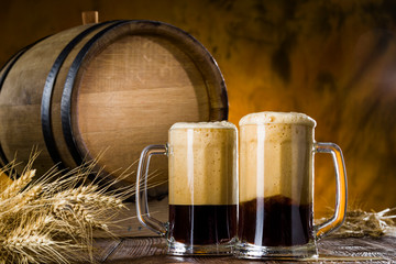 Dark beer with foam in glasses on a wooden table near the barrel,.rye spikelets