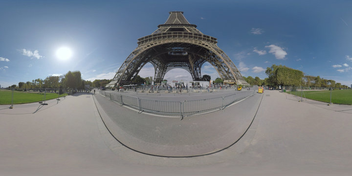 360 photo - City scene with people walking on Gustave Eiffel Avenue near the Eiffel Tower opposite greenspace of Champ de Mars, motorbike rickshaw passing by