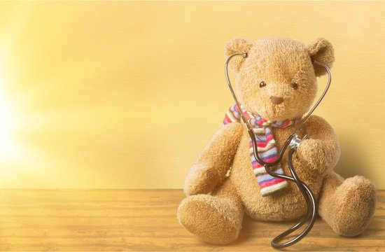 Adorable teddy bear, isolated on white, holding a stethoscope.