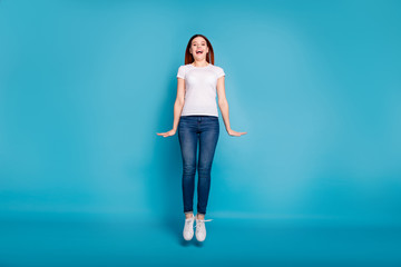 Wall Mural - Full length body size view portrait of her she nice attractive lovely cheerful cheery girl wearing white tshirt having fun jumping up in air isolated over bright vivid shine blue background