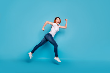 Wall Mural - Full length body size profile side view portrait of her she nice attractive cheerful cheery strong girl wearing white tshirt fast speed isolated over bright vivid shine blue background