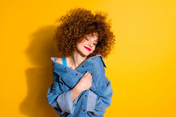 Close-up portrait of her she nice cute lovely charming attractive winsome sweet cheerful wavy-haired girl covering cosy jacket isolated over bright vivid shine yellow background Wall mural