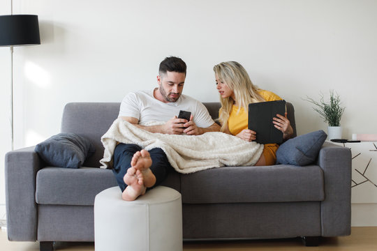 Young casual relaxed couple at home using smartphone and tablet sitting on a sofa. Man and woman with digital online connected devices. Generation Y relationship with technology concept.