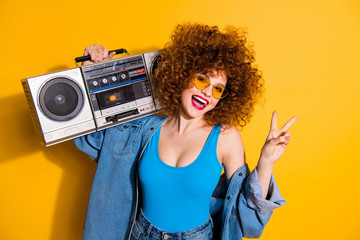 Close up photo beautiful she her lady wavy fluffy styling curls old-fashioned tape recorder show v-sign wear casual jeans denim shirt shorts tank top outfit clothes isolated yellow bright background