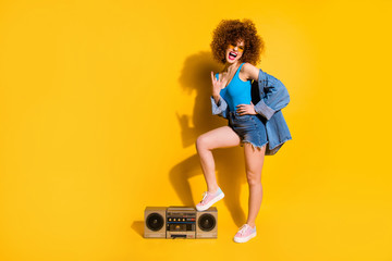 Full length body size photo she her lady wavy styling curls one leg stand old-fashioned tape recorder rocker wear specs casual jeans denim shirt shorts tank top clothes isolated yellow background