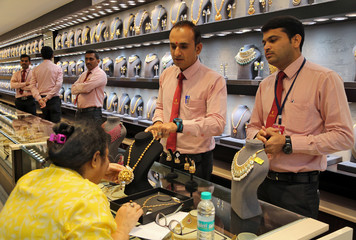 A customer checks a gold necklace before buying it inside a jewellery showroom on the occasion of Akshaya Tritiya, a major gold buying festival, in Mumbai