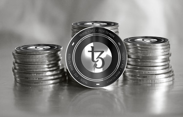 Tezos (XTZ) digital crypto currency. Stack of black and silver coins. Cyber money.