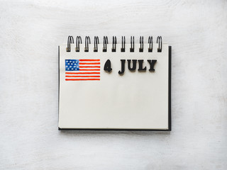 4 JULY. Notepad, American flag drawing and wooden letters of the alphabet on a white table. Close-up. Bright photo and space for your inscriptions. Congratulations to relatives, friends and colleagues