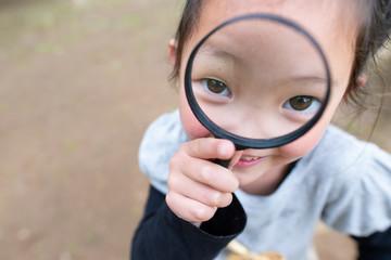 虫眼鏡を使って見る女の子