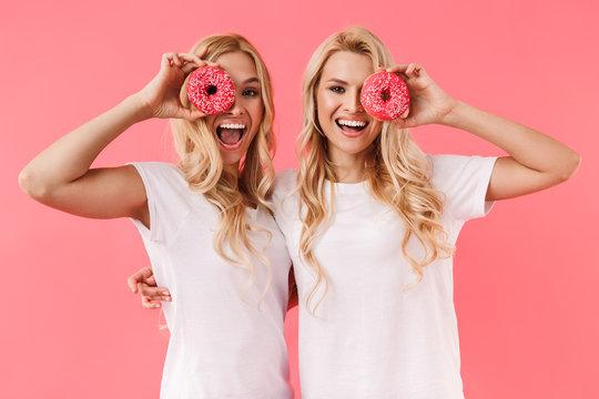 Cheerful blonde twins wearing in t-shirts having fun