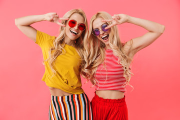 Happy blonde twins in sunglasses showing peace gestures