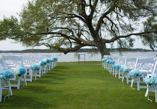 Outdoor wedding venue on the water with hydrangeas hanging from folding chairs.