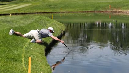 A golfer reaches into a pond to retrieve his ball