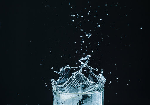 Water splash in glass with black background