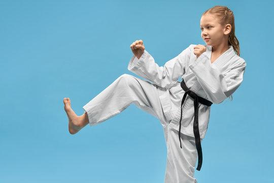 Girl in kimono doing karate on isolated background