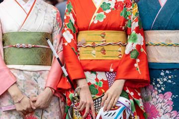 Fototapeta Young girl wearing Japanese kimono standing in front of Sensoji Temple in Tokyo, Japan. Kimono is a Japanese traditional garment. The word