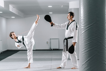 Caucasian handicapped highly motivated girl practicing taekwondo with her training. Girl kicking kick target.
