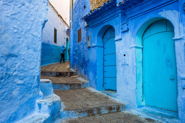 Deurstickers Chefchaouen, Morocco : A child walks in the blue-washed alleyways of the medina old town.