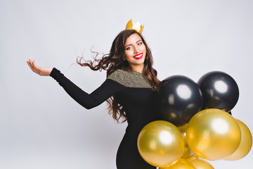 Positive woman on white background celebrating new year, wearing black dress and yellow crown, happy carnival disco party, sparkling confetti, holding yellow and black balloons, having fun