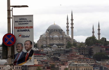 An election banner with the pictures of Turkish President Erdogan and AK Party mayoral candidate Yildirim is seen over the Galata bridge in Istanbul