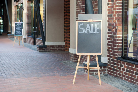 street chalkboard sign display with text sale near shop outdoor