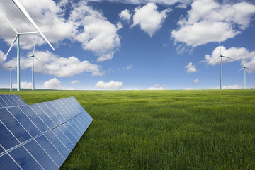 Green energy from the nature concept, solar panels and windmills on green meadow in a summer day
