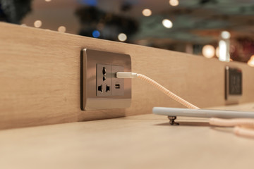 Plug in the charger cable into the phone. Power socket and USB port for Phone charger. Technology concept