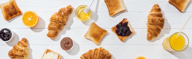 panoramic shot of sweet croissants near tasty toasts and orange juice on white