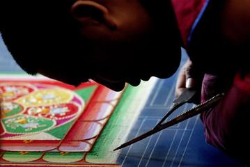 TIBETAN MONK LEANS CLOSE WHILE WORKING ON SAND MANDALA.