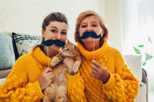 Senior mother and her adult daughter taking selfie with cat using photo booth props at home. Mother's day concept.