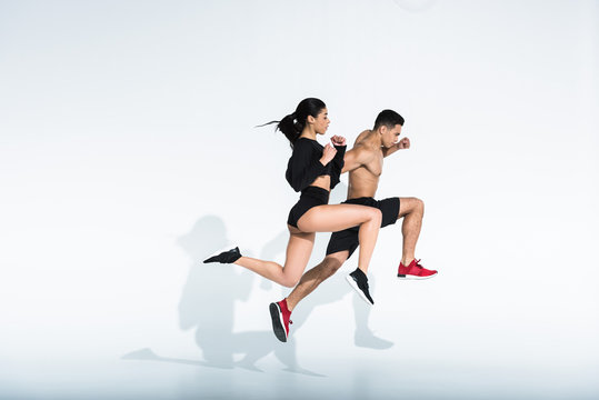 side view of sportive multicultural woman and man in sportswear and sneaker running on white background
