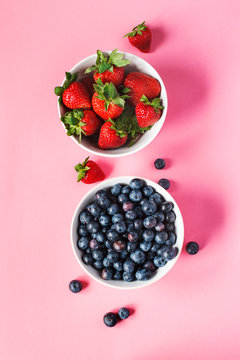 Strawberries and blueberries in bowls on pink background.