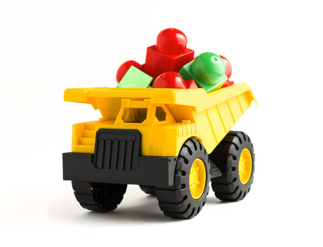 yellow dump truck toy with red and green plastic blocks on white background