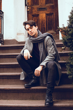 Handsome young man wearing winter clothes sitting on the stairs. Street photo concept.