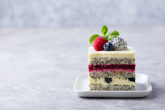 Berry, poppy seed layered cake on white plate. Grey background. Copy space.